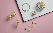 golden bracelets and earrings with pearls on pink and white background