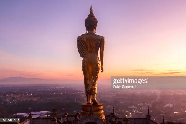 golden buddha statue in khao noi temple at sunrise time, nan province, thailand - deus imagens e fotografias de stock