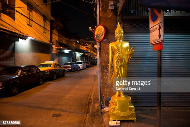 A golden Buddha statue stands by an alleyway at night