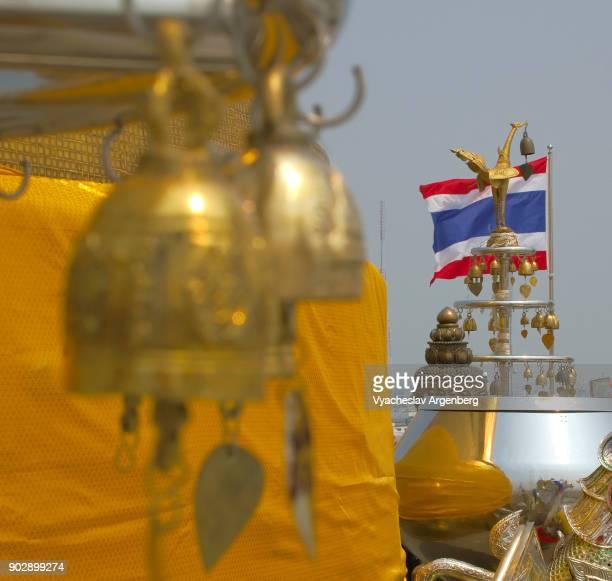 golden buddhist bells and thai national flag at wat saket, bangkok - argenberg stock pictures, royalty-free photos & images