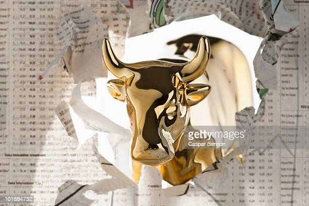 A golden bull breaking through the finance section of a newspaper