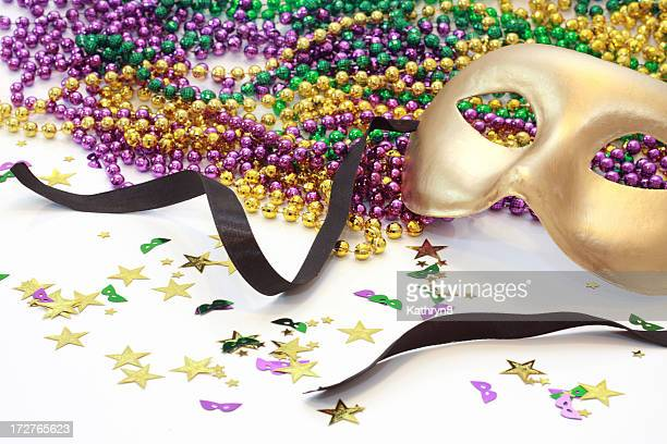 a golden carnival mask and beads - mardi gras beads stock photos and pictures