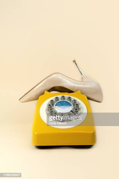 golden color fashion shoe like a telephone receiver of old retro telephone on pastel beige background. - beige shoe stock pictures, royalty-free photos & images