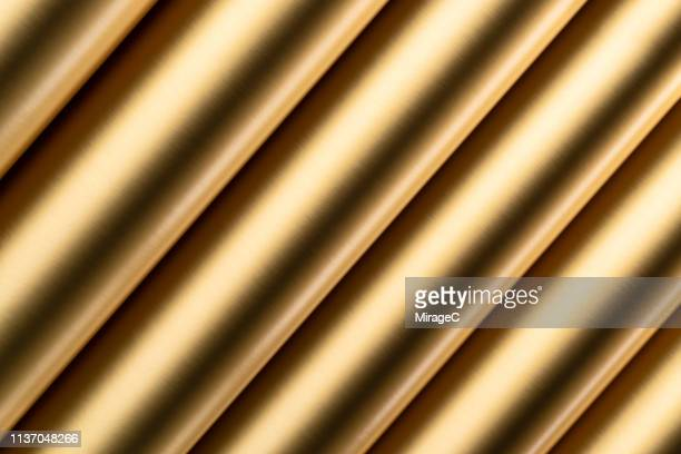 golden colored texture rolled up - cylinder stock pictures, royalty-free photos & images