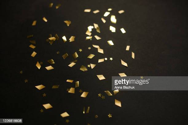 golden confetti over black background. festive abstract glowing background with gold sparkles. - confetti stock pictures, royalty-free photos & images