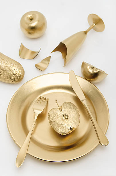 Golden cutlery with apple and bread on white background