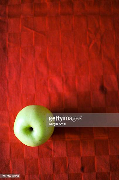 Golden delicious apple on a red table cloth