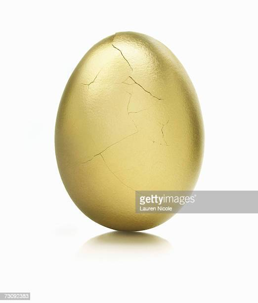 Golden egg, cracks on surface, close up