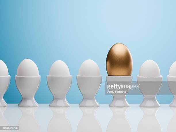 golden egg in egg cup - wealth stock pictures, royalty-free photos & images
