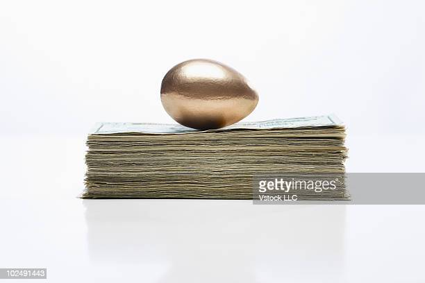 Golden egg on a stack of money