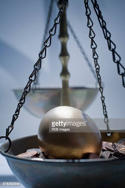 Golden egg on bed of coins in weighing scales