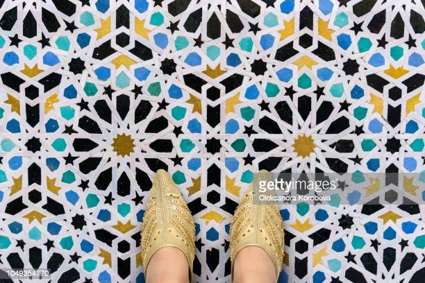 golden embroidered leather slippers or babouches on the intricate ornamental floor decorated with an islamic architectural pattern mosaic. - gold shoe stock photos and pictures