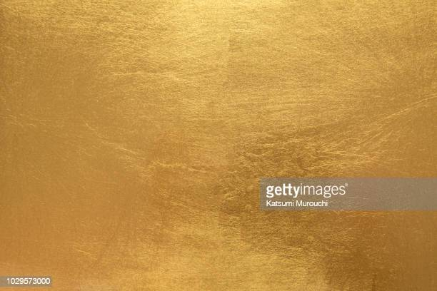 golden foil paper texture background - gold colored stock photos and pictures