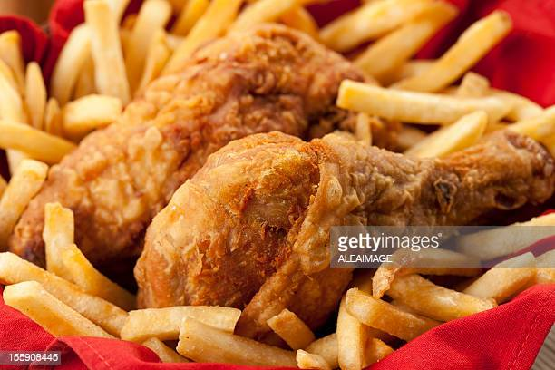 Golden fried chicken on a bed of French fries and red napkin