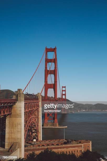 golden gate bridge against blue sky - bortes foto e immagini stock