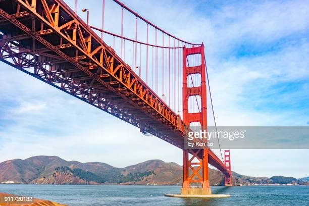 golden gate bridge against cloudy blue sky - ken ilio stock pictures, royalty-free photos & images
