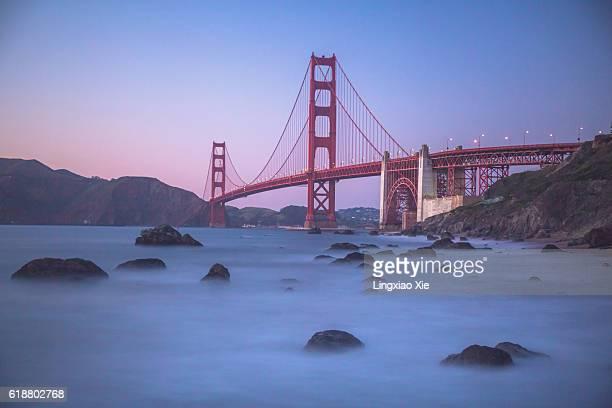 Golden Gate Bridge at dusk with rocks in the ocean, San Francisco