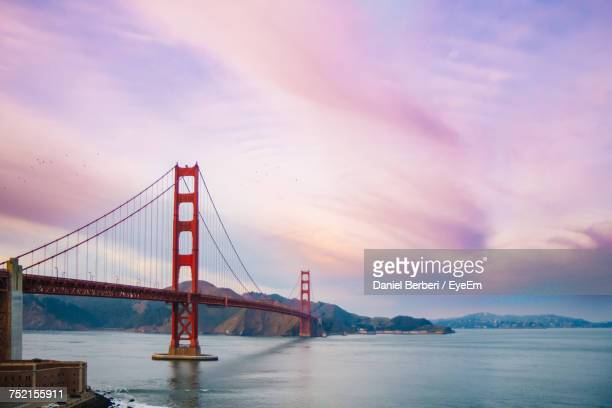 Golden Gate Bridge Over Sea Against Cloudy Sky