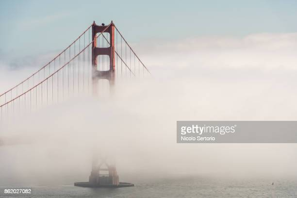 golden gate bridge tower emerging from fog - golden gate bridge stock pictures, royalty-free photos & images