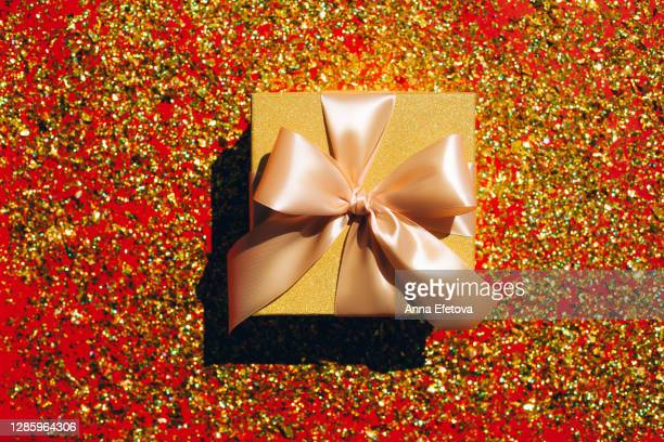 golden gift box near glitter. trendy wrapping of the year - 金曜日 ストックフォトと画像