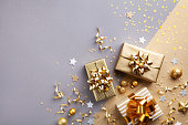 Golden gift or present boxes with golden bows and confetti top view and flat lay. Christmas background.