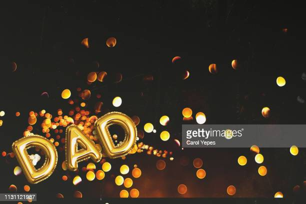 golden glitter ballon with the word dad in black background - junho imagens e fotografias de stock