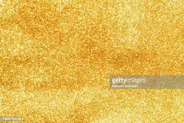 golden glitter powder texture background - gold colored stock pictures, royalty-free photos & images