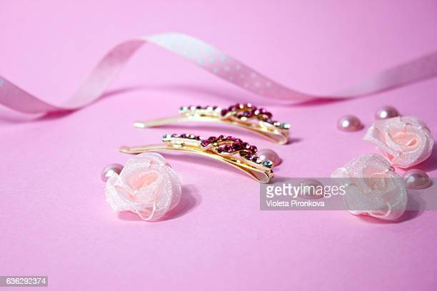 Golden hairpins with pink gemstone and pink polka dot ribbon on pink background