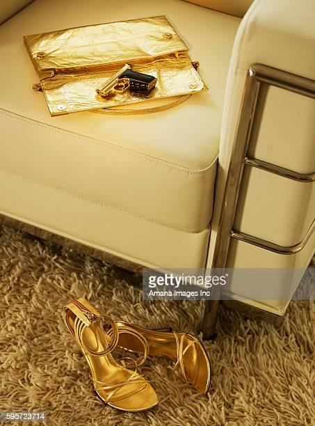 golden handgun and handbag on armchair - gold purse stock photos and pictures