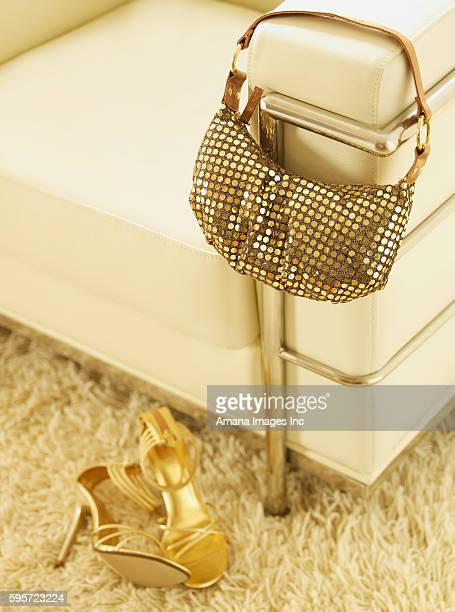 golden high-heeled shoes and handbag by armchair - gold purse stock photos and pictures