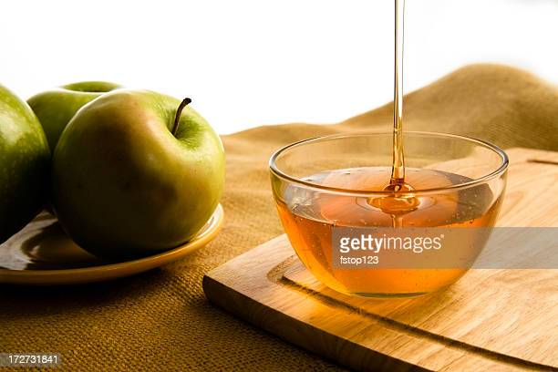 Golden honey poured into clear bowl. Apple. Healthy eating.