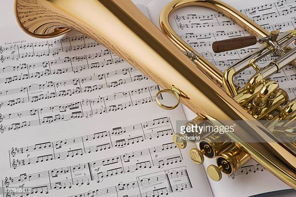 golden horn laying on sheet music - brass stock pictures, royalty-free photos & images
