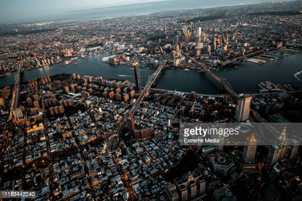 vista aérea de la hora dorada del puente de brooklyn, el puente de manhattan y el puente williamsburg que llega de brooklyn a manhattan, nueva york, tomado desde un helicóptero sobre la isla del bajo manhattan - brooklyn nueva york fotografías e imágenes de stock