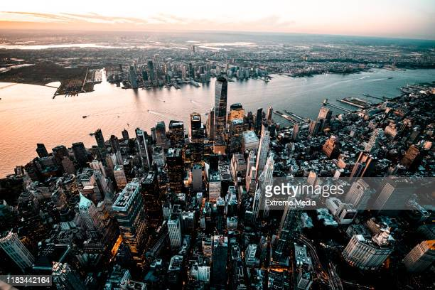 golden hour capture of a downtown lower manhattan skyline overlooking the jersey city, taken from a helicopter - new jersey stock pictures, royalty-free photos & images