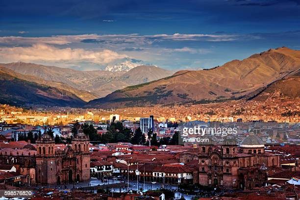 Golden hour high angle view over historic district Plaza de Armas of Cusco, Peru, looking southeast toward snowcapped mountains