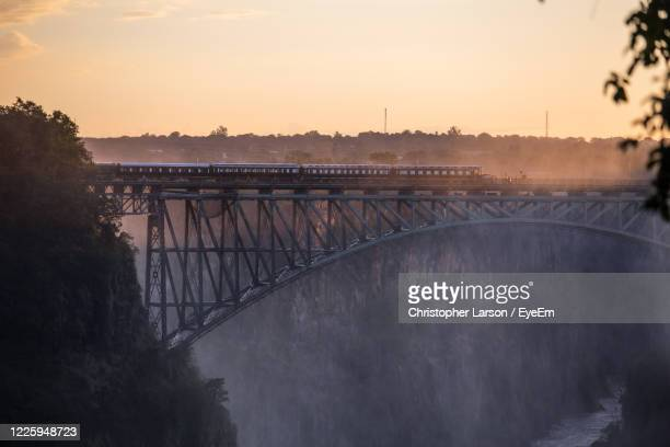 golden hour with bridge and mist at victoria falls zimbabwe. - zimbabwe stock pictures, royalty-free photos & images
