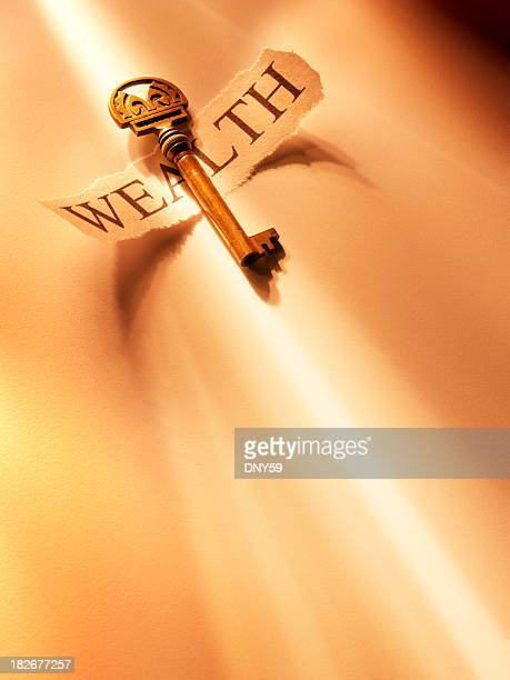 Golden key on torn paper printed  with word wealth