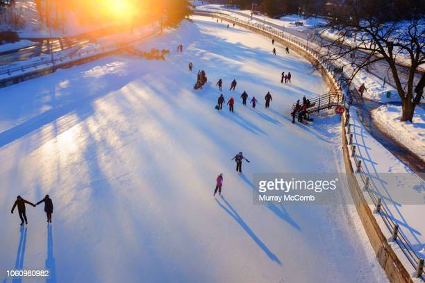 golden light and late day skaters on rideau canal skateway - murray mccomb stock pictures, royalty-free photos & images