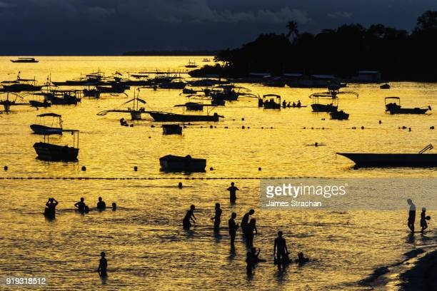 Golden light bathes the sea and highlights the silhouettes of boats and evening bathers, Panglao Beach, Bohol Island, Philippines