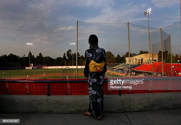 Golden light falls on the Japan Samurai Bears of the independent Golden League as a fan wearing traditional dress takes in the action during a...