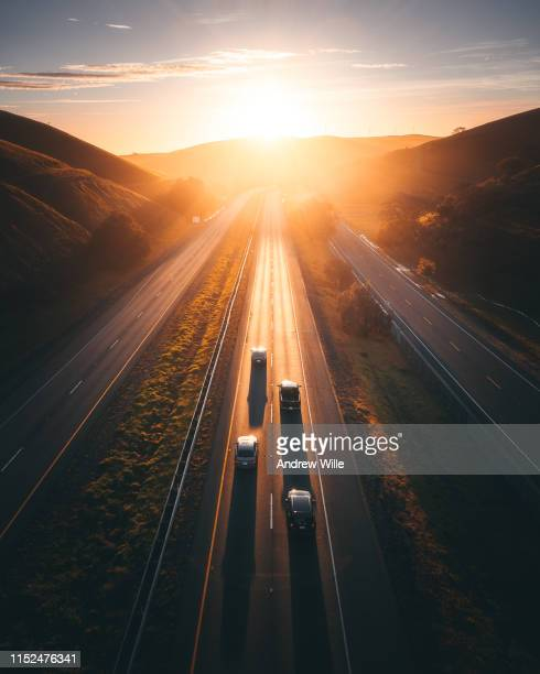 golden light illuminates a remote highway with four cars on it - verkehrswesen stock-fotos und bilder