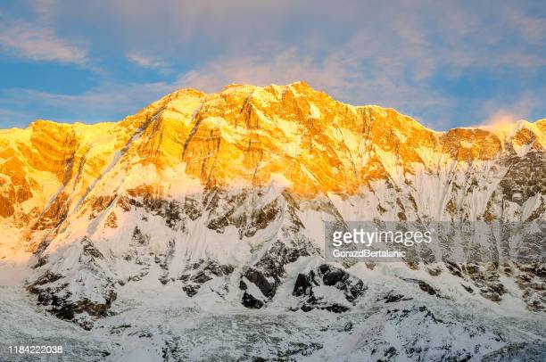 golden light of dawn illuminating the south face of annapurna - himalayas stock pictures, royalty-free photos & images
