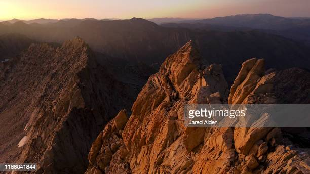 golden light of sunset shining upon the cliffs of the sawtooth ridge seen from the summit of matterhorn peak near bridgeport california on the border of yosemite national park & inyo national forest - pinnacle peak stock-fotos und bilder