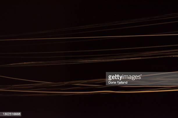 golden light on black wires against a black background - dorte fjalland fotografías e imágenes de stock