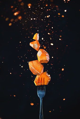 Golden marmalade block on a fork with sparks and flares. Action food photography on a dark background with copy space. Gourmet dessert concept. - gettyimageskorea