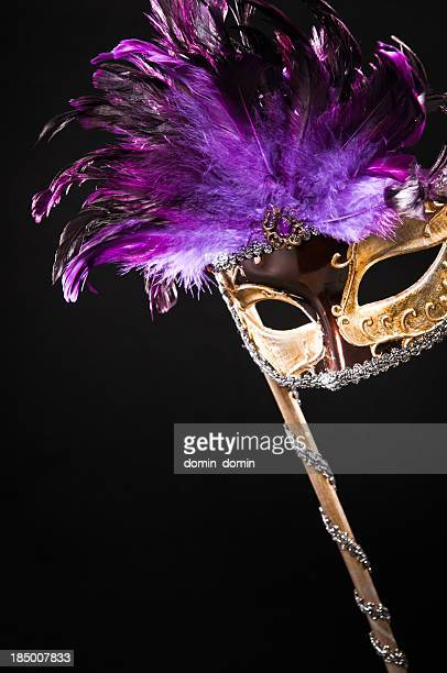 Golden masquerade carnival mask with purple feathers