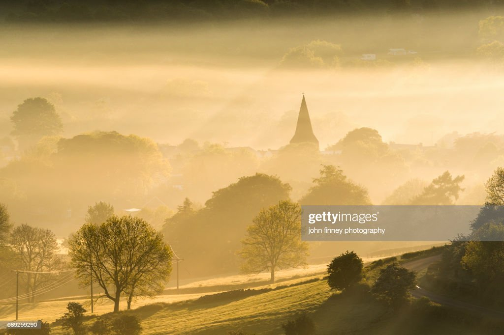 Golden mist at sunrise with the Parish church of St Peter, Hope village. English Peak District. UK. : Stock Photo