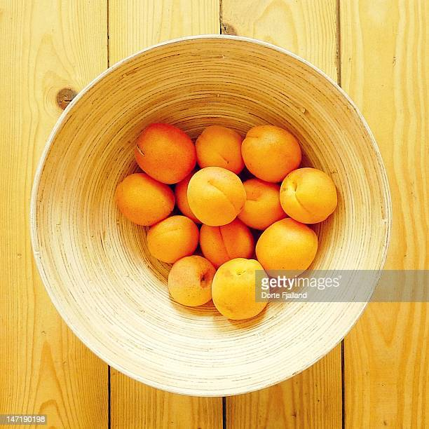 Golden orange apricots in wooden bowl