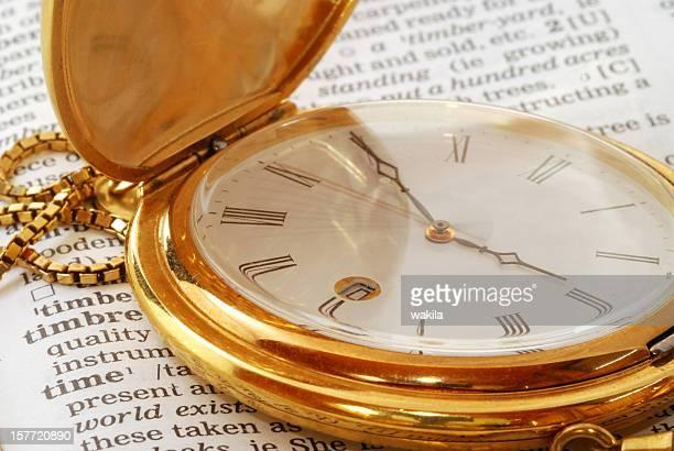 Orologio da tasca dorato sul dizionario tempo