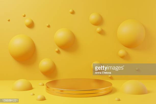 golden podium on yellow background with spheres. perfect for beuty products demonstration. - achtergrond thema stockfoto's en -beelden